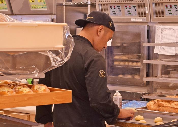 厨房釜担当のユニフォーム。帽子とコックコートにゴールドのロゴ刺繍